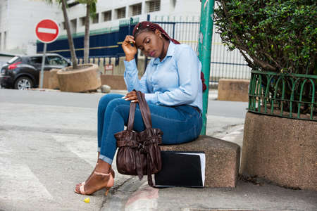 Businesswoman sitting alone on the street with her documents and bag, feeling worried and stressed after a day of searching for work in the city. Stock fotó