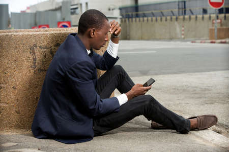 young african man sitting in a suit looking at mobile phone. 免版税图像