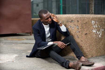 young african man sitting on the floor in a suit thinking with mobile phone in hand.