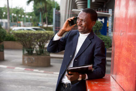 young african man standing in suit go talk to mobile phone laughing.
