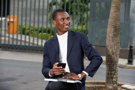 young african man sitting in suit with mobile phone looking in profile while smiling. 免版税图像