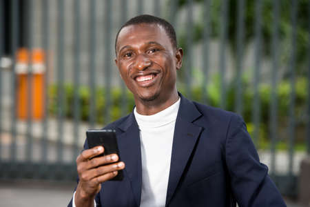 young african man standing in suit with mobile phone looking at camera laughing.