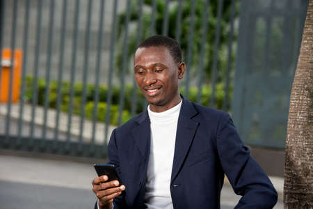young african man sitting in a suit looking at mobile phone while smiling.