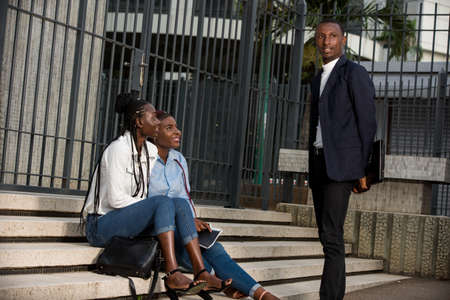 group of three people social workers standing man and women sitting on the stairs and talking about their work in the morning with the background of urban space