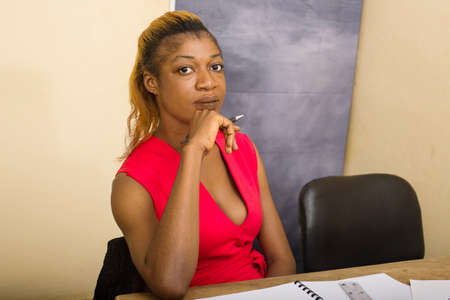 Young business woman meditating with hand on chin in office. Decision making concept