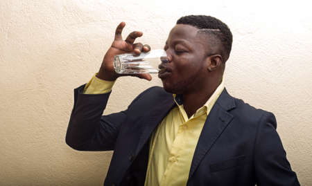 young businessman in suit standing inside and drinking water in a glass