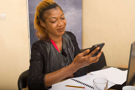 Portrait of beautiful young woman sitting at her desk and using a mobile phone.concept communication and business