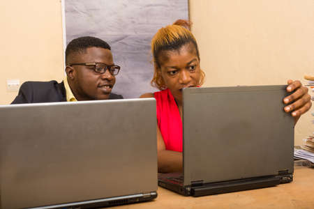 Teamwork: businessman and businesswoman working in office, they discuss and work on laptop.