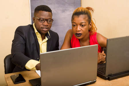 Teamwork: Businessman and businesswoman working as a team in office, they discuss and work on laptop.