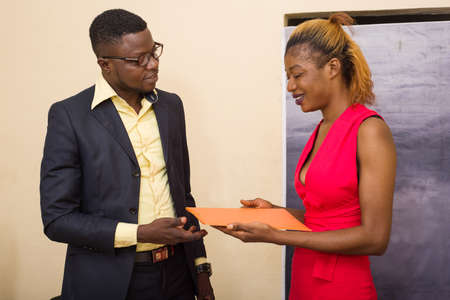 Two business men: young woman giving an orange folder to her colleague in the office after the meeting Foto de archivo