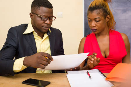 Businessman and businesswoman discussing articles about a new business plan during a meeting at the office, colleagues preparing important documents for the work, concept of teamwork