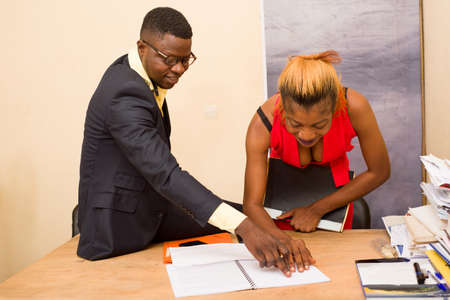 young businessman in office suit doing check in notebook with his secretary smiling.