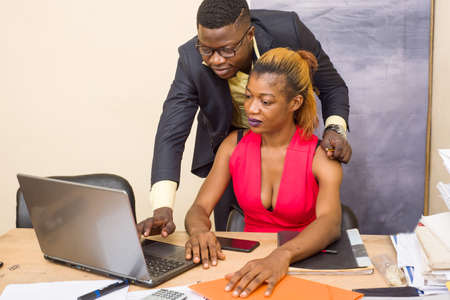 Young and beautiful business people work together on a desktop in a modern office.