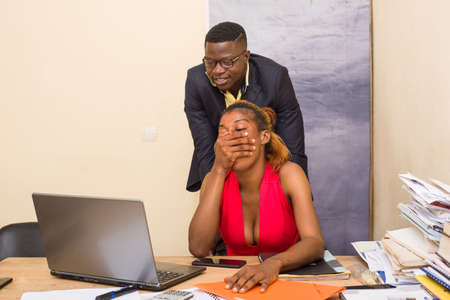 young and beautiful business people working together on a desktop in a modern office and looking at something funny. Woman sitting in front of a desk closes his mouth