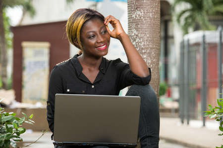 young woman sitting alone outdoors and looking pensive and smiling while holding a laptop on her feet