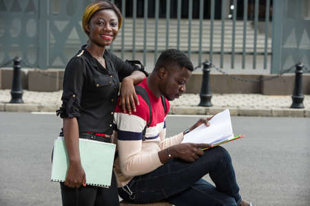 Two African student friends study together outdoors. Man seated on concrete and the girl is standing near him.