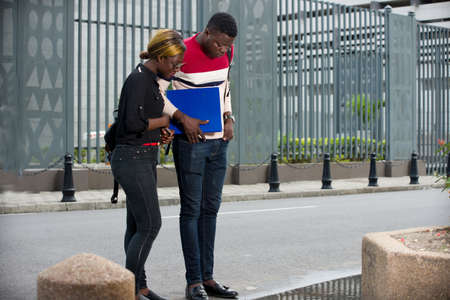 woman and an education man or students discuss after school instructions while walking together on the street