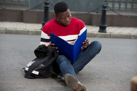 Handsome college man reading notes in notebook on campus.Happy student learning outdoors sitting outside. Education