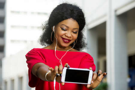 Beautiful young woman using laptop on a modern mobile phone with screen to copy text promotional content ...