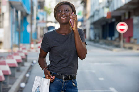 young girl talking on the phone while walking down the street after shopping in the city
