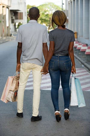 Portrait of a happy couple with shopping bags walking together in city.