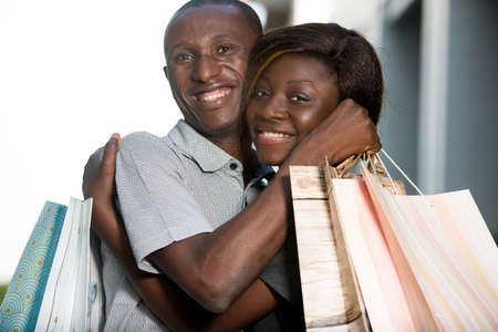 Portrait of young smiling couple kissing and holding shopping bags Imagens