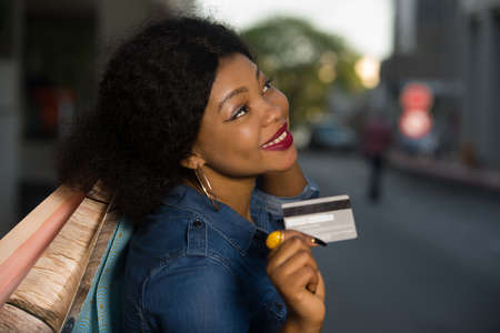 Portrait of smiling woman with a credit card and shopping bags in a hand in town