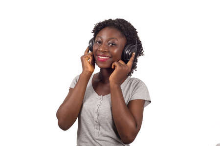 Young happy woman enjoying listening to the music from headphones isolated on a white background