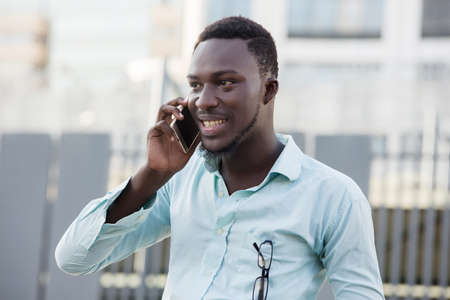 Portrait of modern man and talking on the phone visiting the city street,