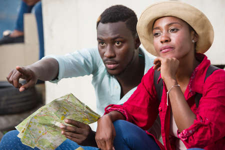 young man sitting with his girlfriend girl geographical map in hand showing him something while she dreams.