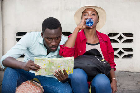young tourist couple sitting in jeans with map. Imagens