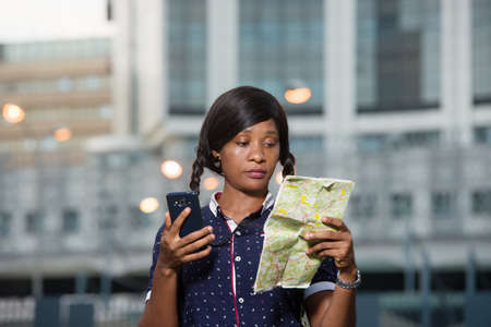 young tourist woman standing outdoors looking at map with mobile phone in hand.
