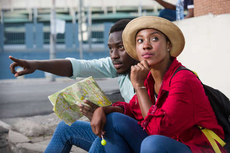 young man sitting with his girlfriend geographical map in hand showing him something but that one seems to dream.