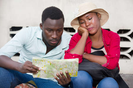 young couple of tourists sitting in jeans staring with map. Imagens