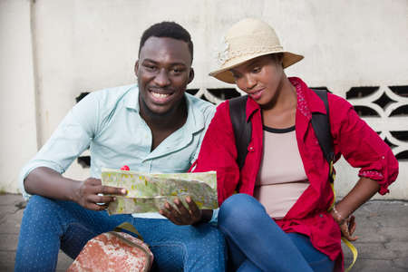 young tourist couple sitting in jeans with map smiling.