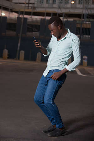 young man standing outdoors looking at mobile phone looking surprised.