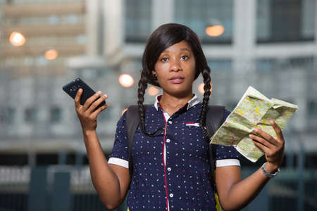 Young tourist woman standing outdoors looking at camera with map and mobile phone in hand. Imagens