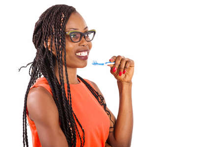 young girl standing in eyeglasses on white background smiling to hold toothbrush to chin.
