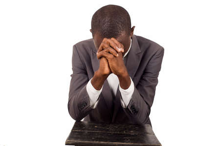 portrait of young pastor kneeling and praying with head down.