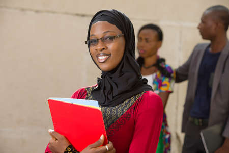 young muslim woman standing in eyeglasses outdoors looking at camera smiling.