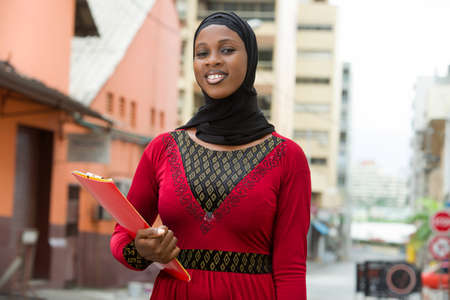 young muslim female student standing outdoors looking at camera smiling. Stockfoto
