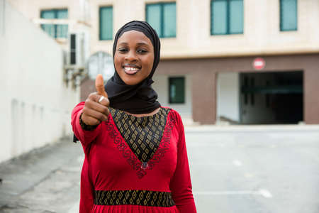 young woman standing outdoors with veil smiling to camera making thumb gesture. Stockfoto