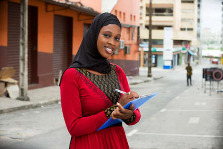 muslim student girl standing outdoors taking notes and looking at camera smiling.