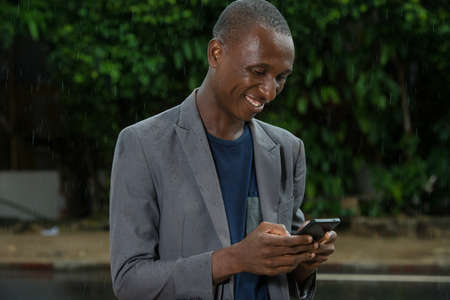young man standing under a light rain looking at mobile phone while smiling.