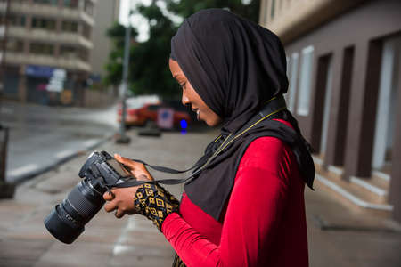 portrait of young muslim woman with camera, smiling.