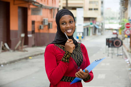 young muslim female student standing outdoors looking at the camera smiling with a notebook.