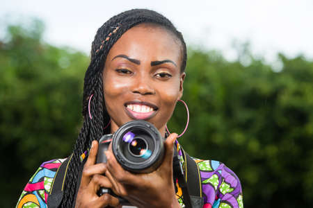 young woman standing right in front of camera with a camera smiling. Stockfoto