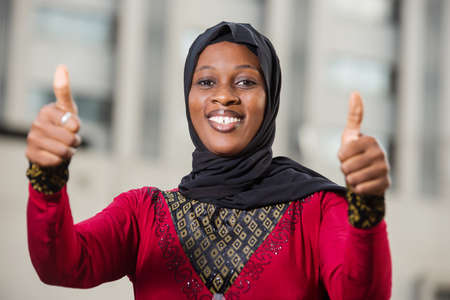 young muslim woman standing outdoors looking at camera laughing with thumbs up.