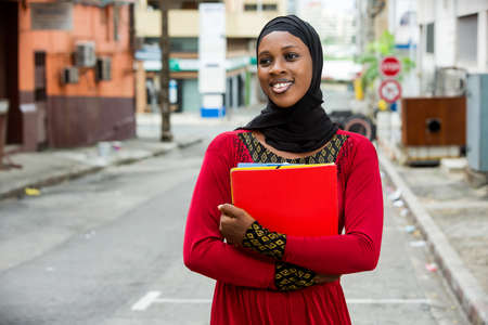 Muslim girl standing outdoors with documents smiling at the camera. Stockfoto