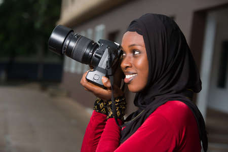 young muslim woman standing outdoors looking at camera smiling. Stockfoto
